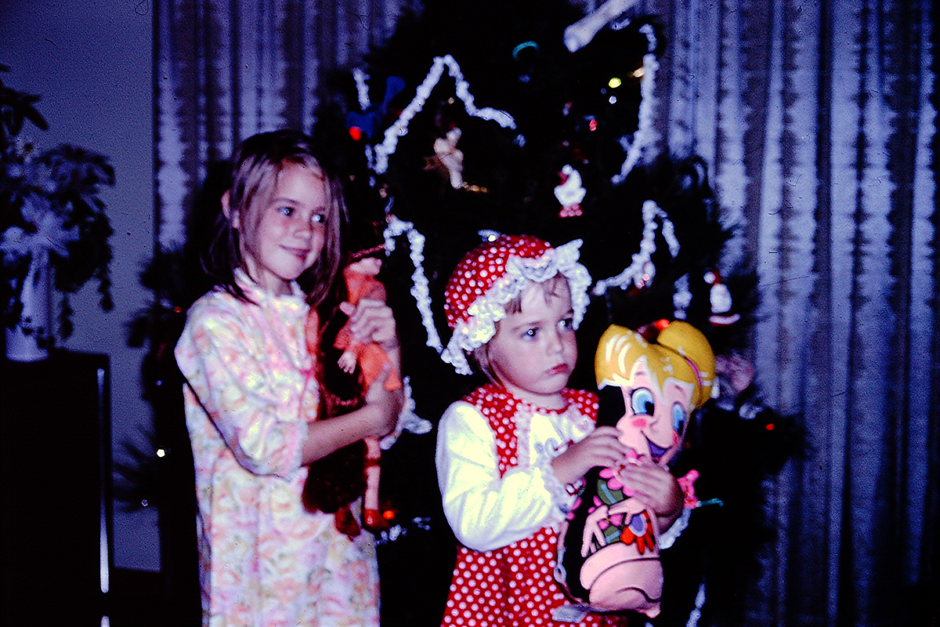 Melanie and Missy as children holding their dolls at Christmas. Melanie holds Chrissy and Missy holds Tinkerbell.