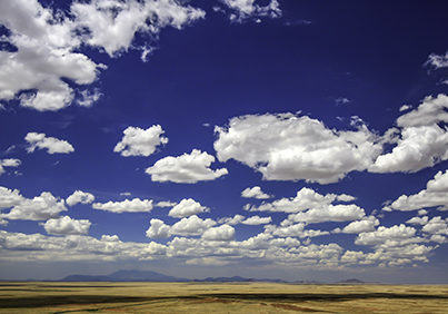 Photograph of clouds in Arizona with mountains on the distant horizon.  Taken by Melissa Whitaker